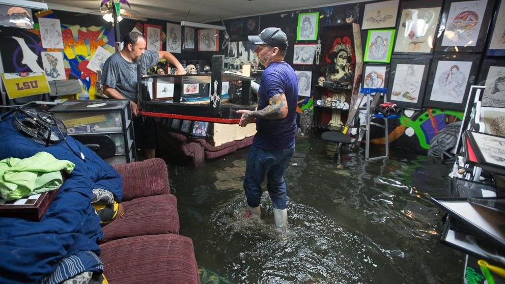 Brad Gilbert, left, helps his friend Mike Abel with his flooded business in Amite, Louisiana, picking up anything that is salvageable before the water gets higher, Aug. 12, 2016.