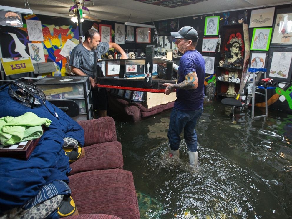 PHOTO: Brad Gilbert, left, helps his friend Mike Abel with his flooded business in Amite, Louisiana, picking up anything that is salvageable before the water gets higher, Aug. 12, 2016.