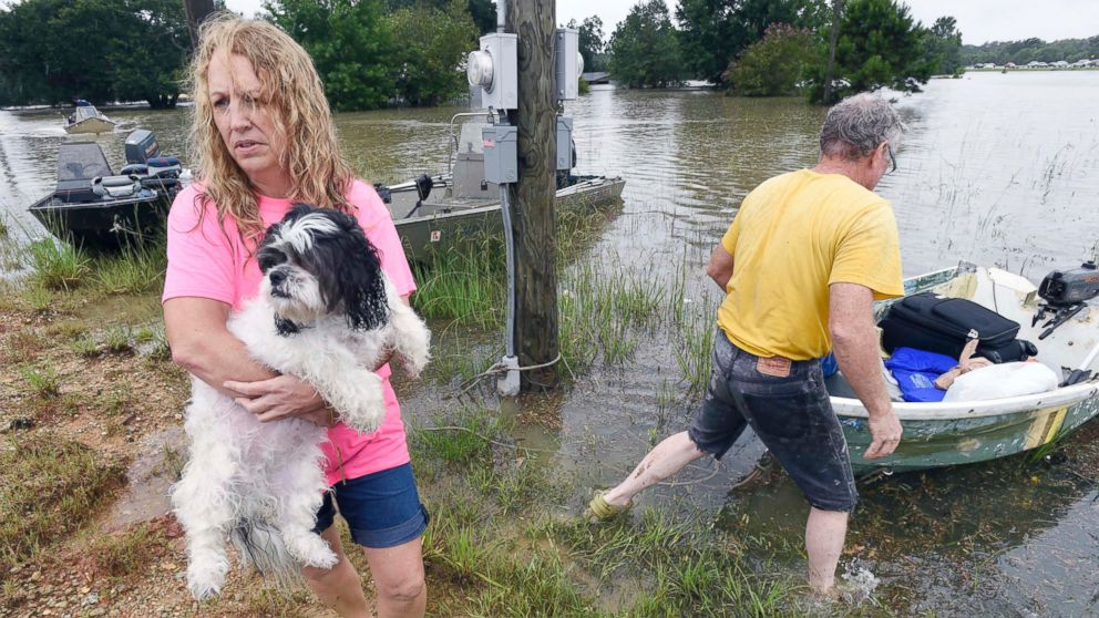 Tammie Wise holds her dog Mikey, after Jeffrey Lesage, right, boated them to safety in Central, Louisiana, Aug. 13, 2016.