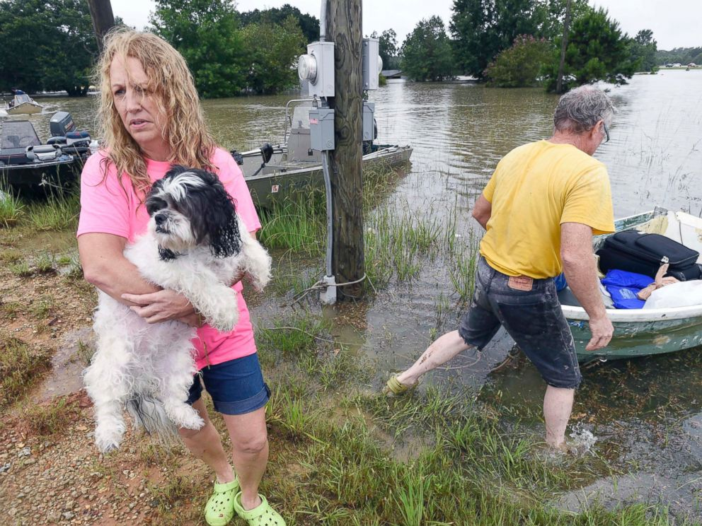 PHOTO: Tammie Wise holds her dog Mikey, after Jeffrey Lesage, right, boated them to safety in Central, Louisiana, Aug. 13, 2016.