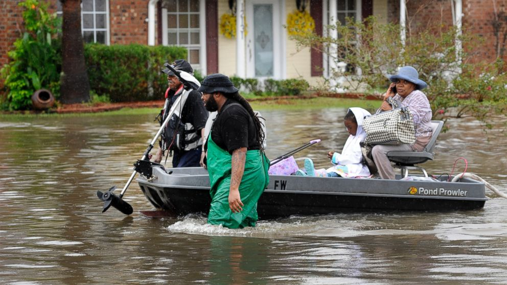 Volunteers pull a boat with a woman and young child as they evacuate from their homes, Aug. 13, 2016, in Baton Rouge, Louisiana.
