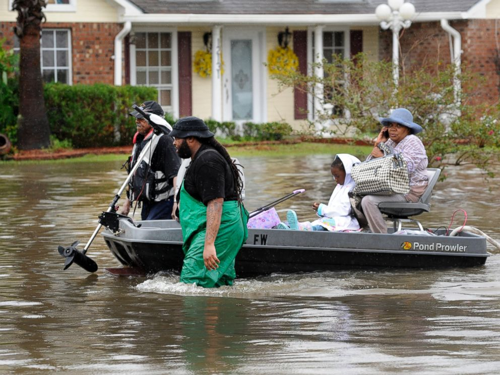 PHOTO: Volunteers pull a boat with a woman and young child as they evacuate from their homes, Aug. 13, 2016, in Baton Rouge, Louisiana.