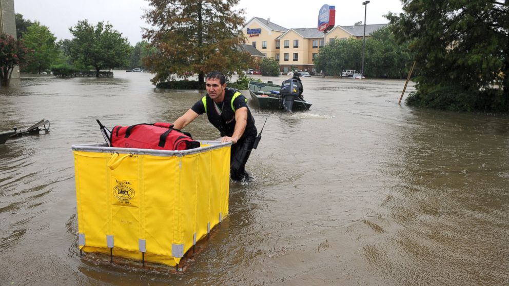 A Lafayette firefighter brings guests luggage to the street while evacuating them from the Fairfield Inn in Lafayette, Louisiana, Aug. 13, 2016.