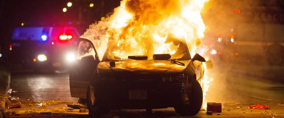 PHOTO: A car burns as a crowd of more than 100 people gathers following the fatal shooting of a man in Milwaukee, Aug. 13, 2016.