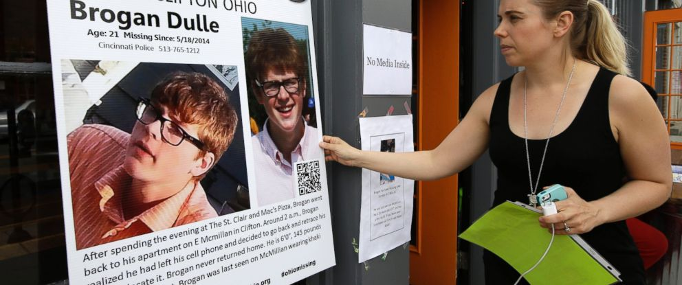 PHOTO: Laura Lewis, spokesperson for the family of missing University of Cincinnati student Brogan Dulle, adjusts a sign near the university campus, May 22, 2014, in Cincinnati.