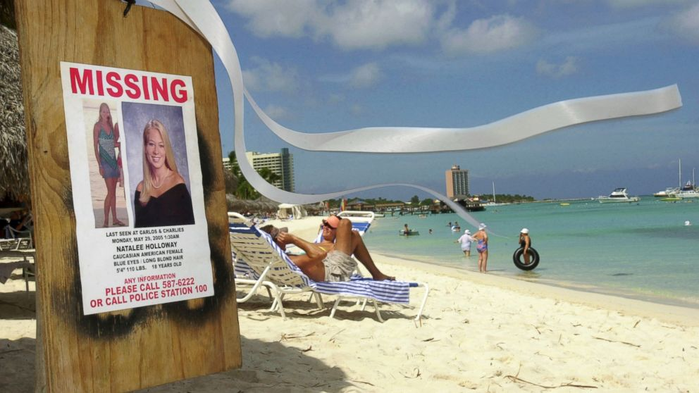 A missing poster for Natalee Holloway, a high school graduate of Mountain Brook, Alabama who disappeared while on a graduation trip to Aruba on May 30, 2005, is seen on Palm Beach where tourists sunbathe in Aruba, June 10, 2005.