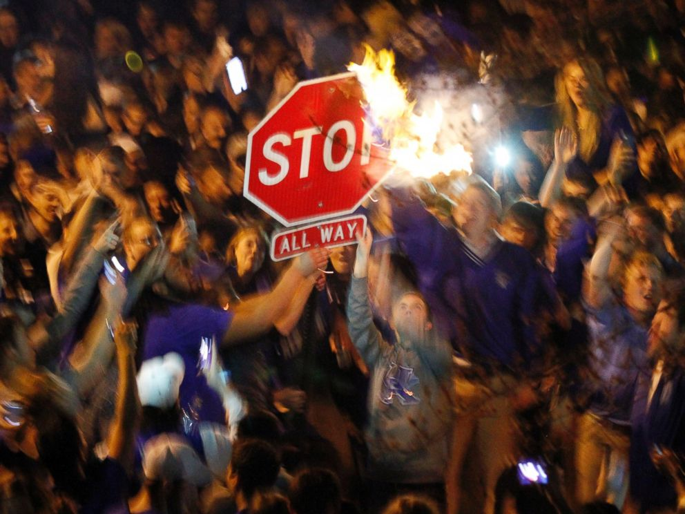 PHOTO: Kentucky fans wave a stop sign with a burning shirt near the University of Kentucky campus, Saturday, April 5, 2014, in Lexington, Ky.