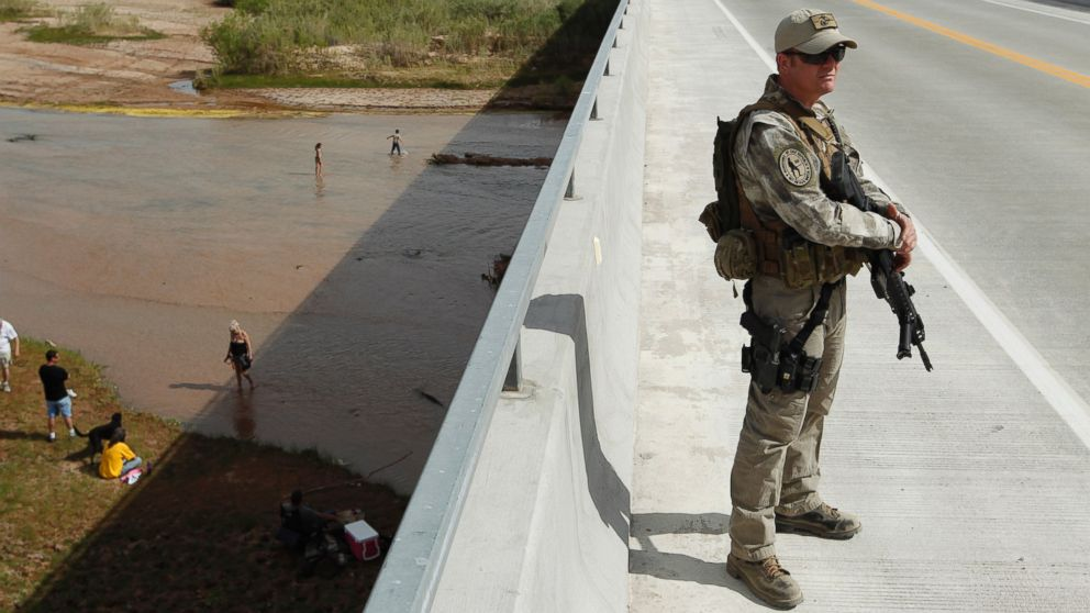 Justin Giles of Wasilla, Alaska stands guard on a bridge over the Virgin River during a rally in support of Cliven Bundy near Bunkerville, Nev. Friday, April 18, 2014.