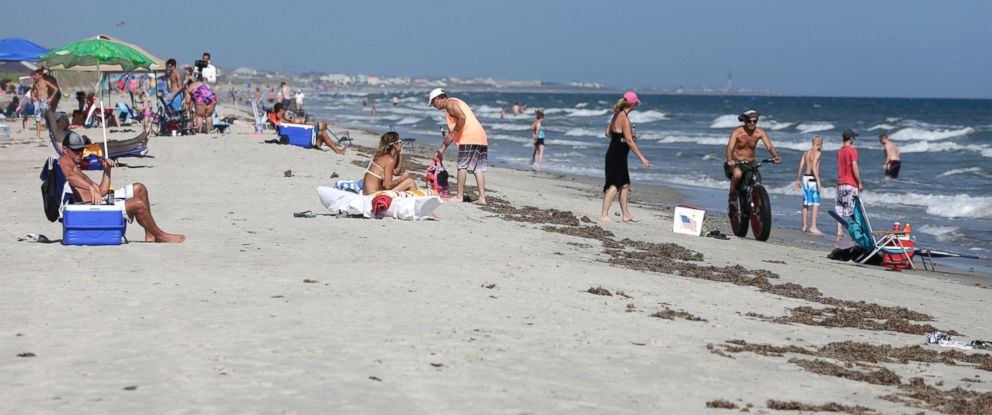 PHOTO: Vacationers relax on the bench and in the surf in Oak Island, N.C., June 15, 2015.