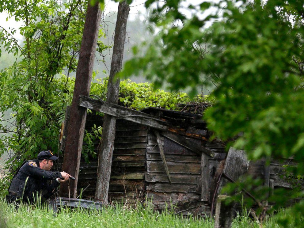 PHOTO: A law enforcement officer checks a broken down building for escaped prisoners near Essex, N.Y., June 9, 2015.