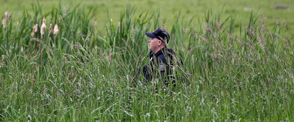 PHOTO: A law enforcement officer walks through a swampy area searching for escaped prisoners near Essex, N.Y., June 9, 2015.