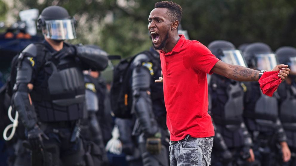 A protester yells at police in front of the Baton Rouge Police Department headquarters after police arrived in riot gear to clear protesters from the street in Baton Rouge, Louisiana, July 9, 2016.