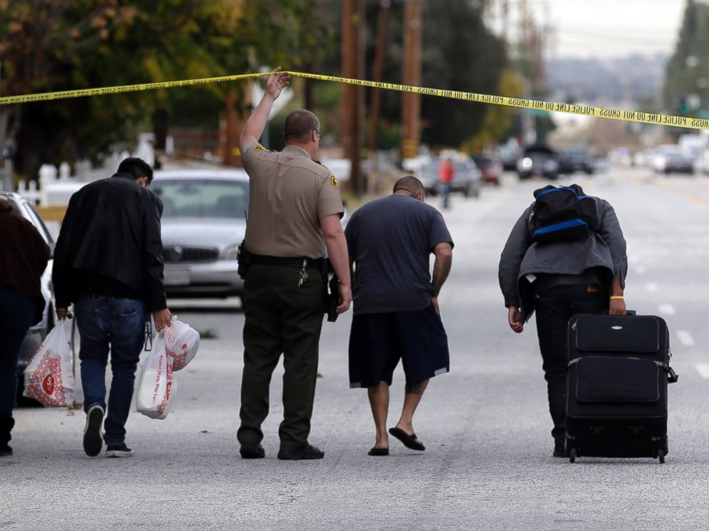 PHOTO: Residents are escorted to their homes near a Black SUV that was involved in a police shootout with shooting suspects, Dec. 3, 2015, in San Bernardino, Calif.
