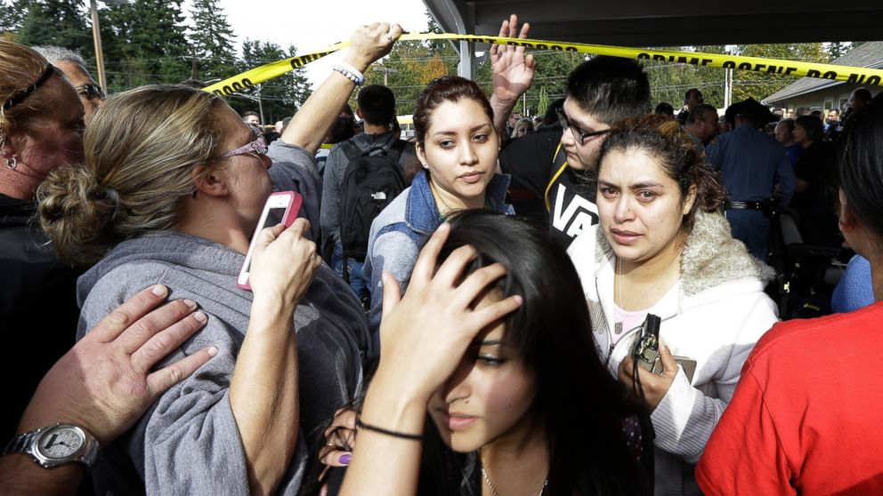 Parents and students move under police tape at a church, where students were taken following a shooting at Marysville Pilchuck High School in Marysville, Wash. on Oct. 24, 2014.