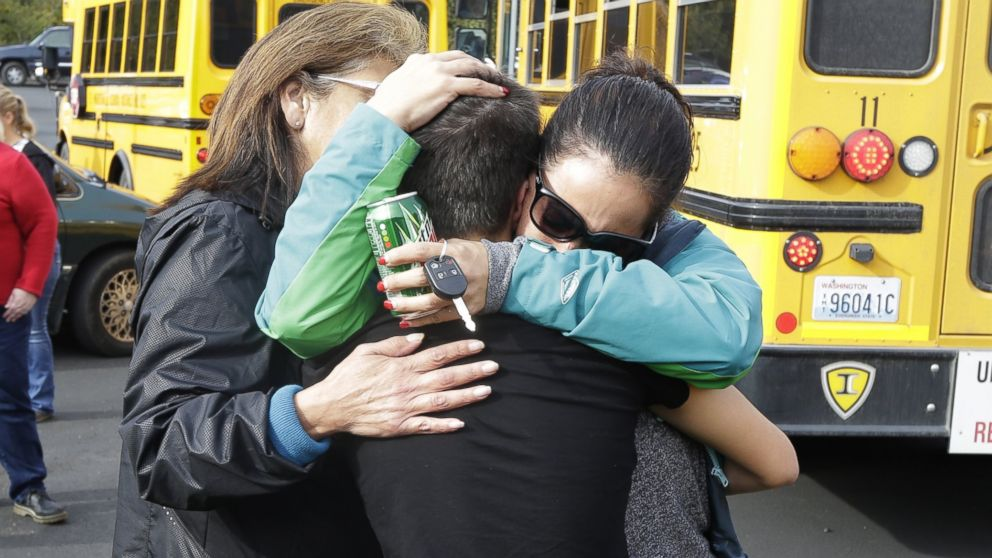 People embrace in front of school buses at a church, where students were taken to be reunited with parents, following a shooting at Marysville Pilchuck High School in Marysville, Wash. on Oct. 24, 2014.