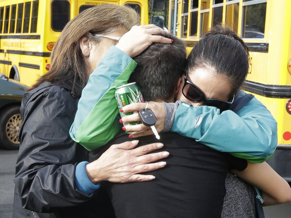 PHOTO: People embrace in front of school buses at a church, where students were taken to be reunited with parents, following a shooting at Marysville Pilchuck High School in Marysville, Wash. on Oct. 24, 2014.