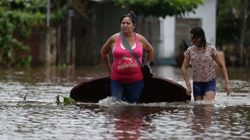 Maria Cristina Olivera and her daughter Catherin carry a table on a flooded street as they leave their home in San Miguel neighborhood in Asuncion, Paraguay, Dec. 27, 2015.
