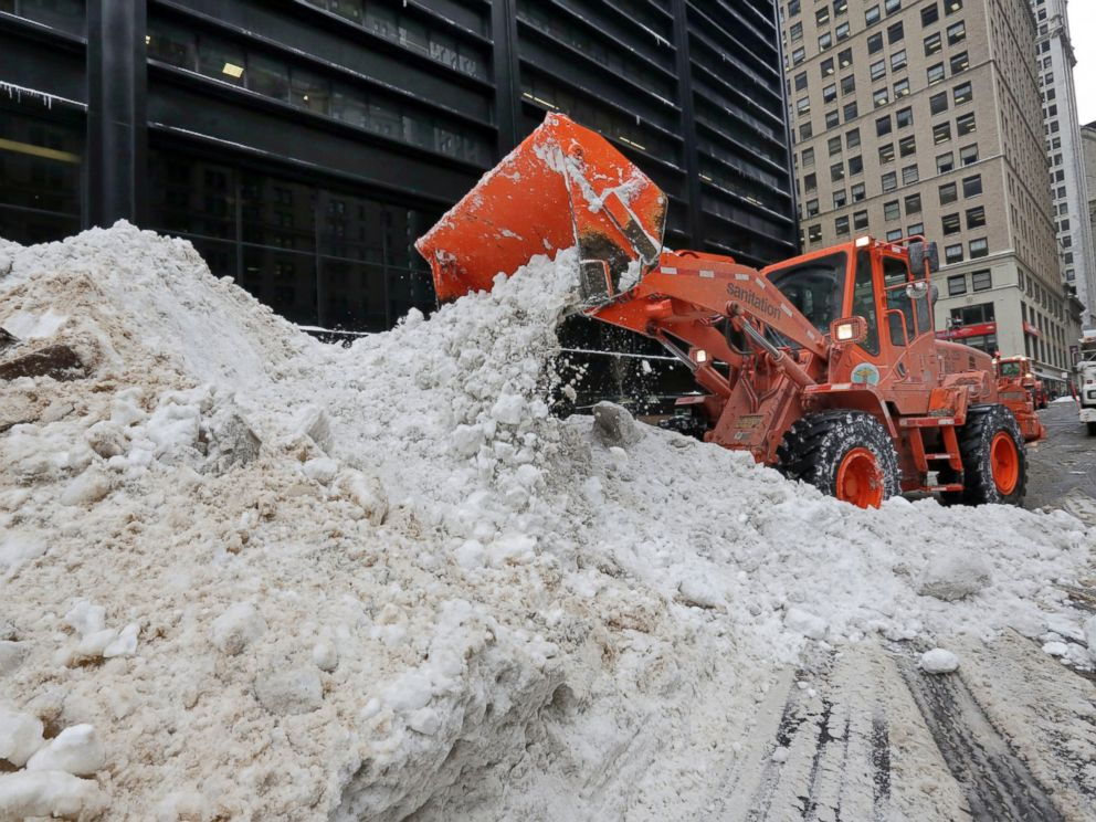 PHOTO: A New York City Department of Sanitation front end loader unloads collected snow for melting, near the World Trade Center site, in New York, Jan. 25, 2016.