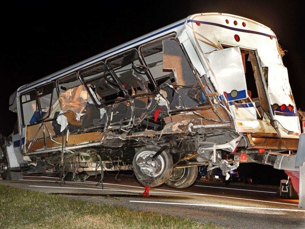 A wrecker removes the team bus as Highway Patrol and emergency personnel work the scene of a crash just south of the Turner Falls area on Saturday, Sept. 27, 2014 in Davis, Okla. Four members of a Texas college softball team died in the crash.