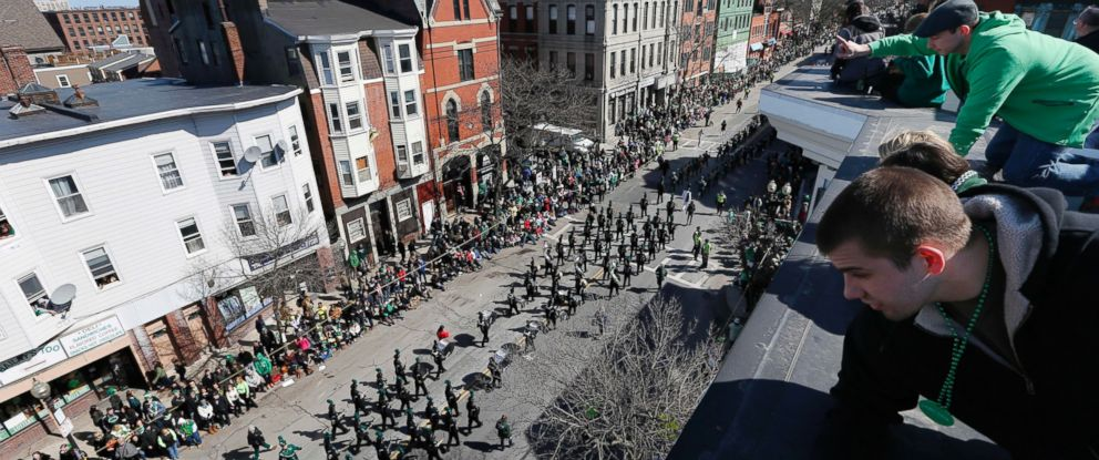 PHOTO: People watch the annual St. Patricks Day parade from a roof in the South Boston neighborhood of Boston, March 16, 2014.