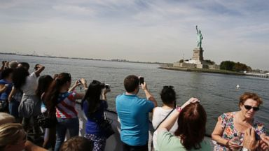 PHOTO: Tourists take photos of the Statue of Liberty on Thursday, Oct. 3, 2013.