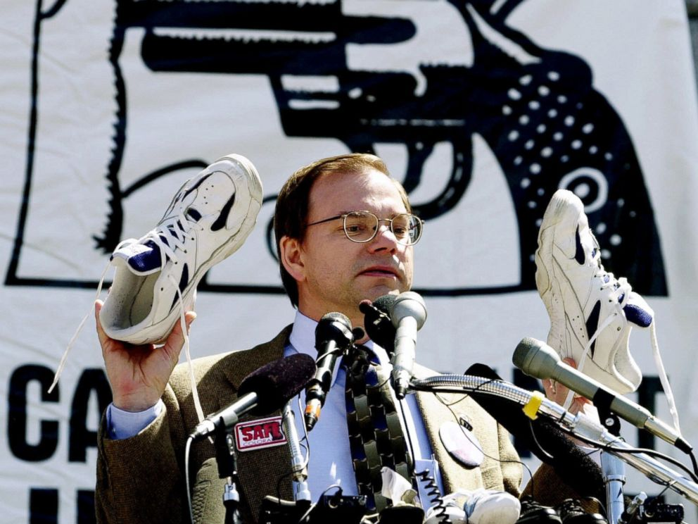 PHOTO: Tom Mauser holds up a pair of shoes belonging to his late son, Daniel, who was killed in the Columbine High School shooting, during a rally at the Capitol in Denver, April 11, 2000.