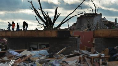 PHOTO: Residents search through a neighborhood in Washington, Ill., after a tornado and strong thunderstorms swept through the north part of the town destroying several homes, Nov. 17, 2013.