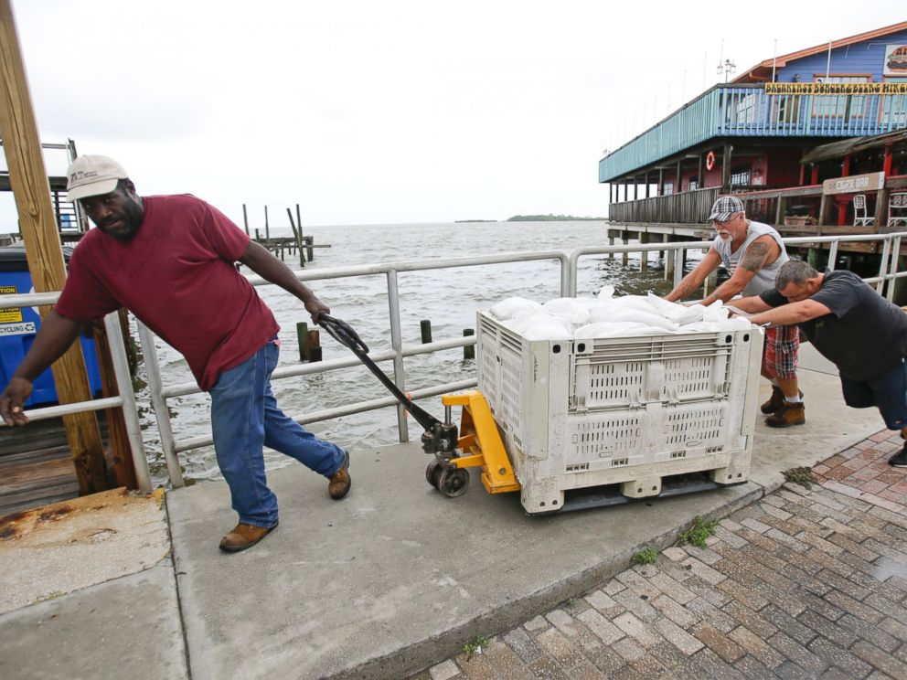 PHOTO: Workers move sandbags to protect a restaurant in preperation for Tropical Storm Hermine, Aug. 31, 2016, in Cedar Key, Florida.