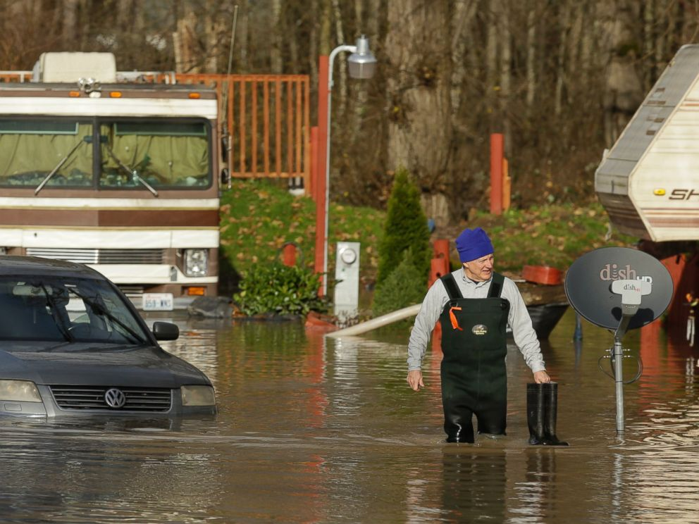 PHOTO:Mike Ewing, co-owner of the Riverview RV Park, wades through floodwaters near a partially submerged car, Dec. 9, 2015, in Puyallup, Wash., after he hooked up a pump to get rid of water that flooded RVs and other vehicles Wednesday morning.