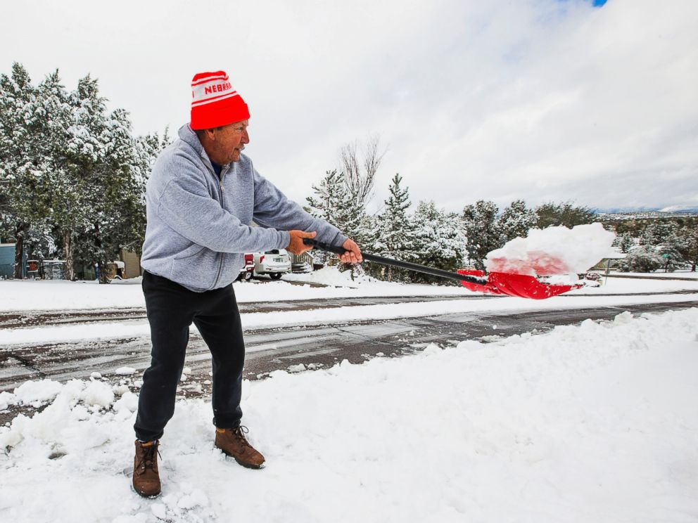PHOTO: David Rutter shovels on his driveway after snow fell covering the area with a few inches in Payson, Ariz., Dec. 14, 2015.
