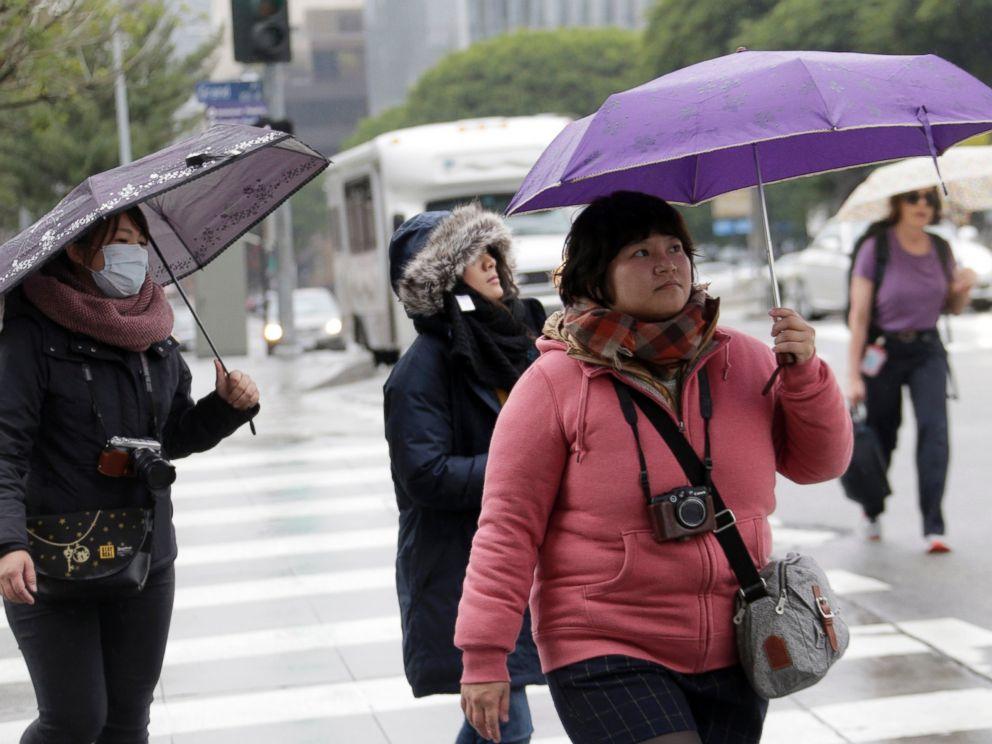 PHOTO: Pedestrians walk under a light rain downtown Los Angeles, Dec. 22, 2015.