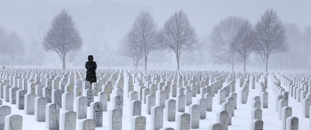 PHOTO: A woman visits a gravesite in the Fort Snelling National Cemetery during a snowstorm in Minneapolis, March 23, 2016.