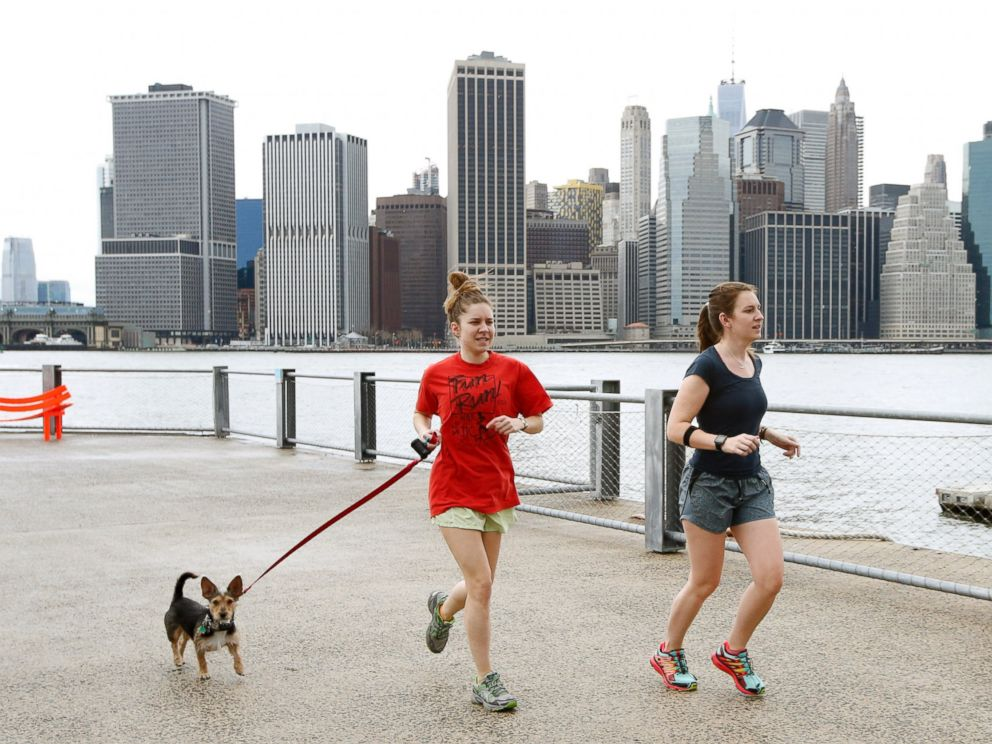 PHOTO: Joggers dressed in shorts and T-shirts run in Brooklyn Bridge Park, in New York, as the Lower Manhattan skyline is seen behind them, Dec. 24, 2015.
