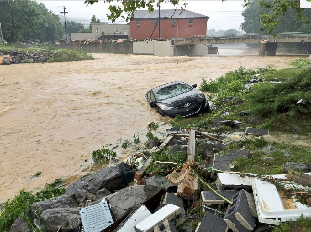 In this photo released by The Weather Channel, a vehicle rests in a stream after heavy rain near White Sulphur Springs, W.Va., June 24, 2016.