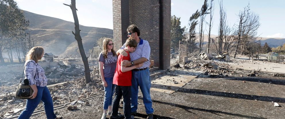 PHOTO: A family stands in front of the remains of their fire-destroyed home, June 29, 2015, in Wenatchee, Wash.