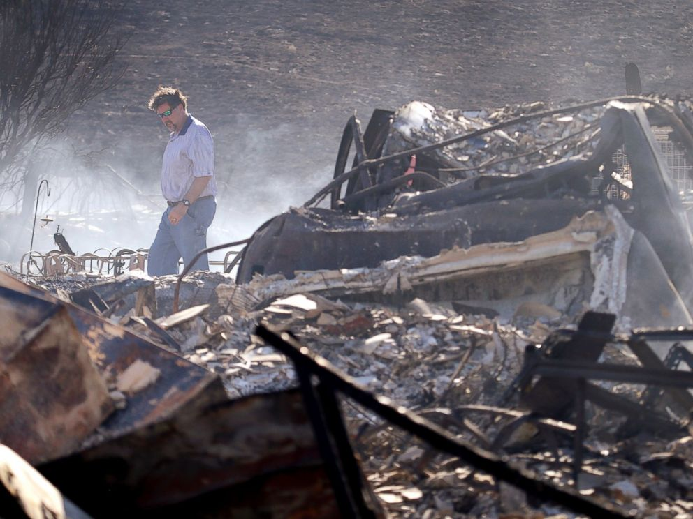 PHOTO: A man walks through the rubble of his still smoldering home, destroyed in a wildfire the night before, June 29, 2015, in Wenatchee, Wash.