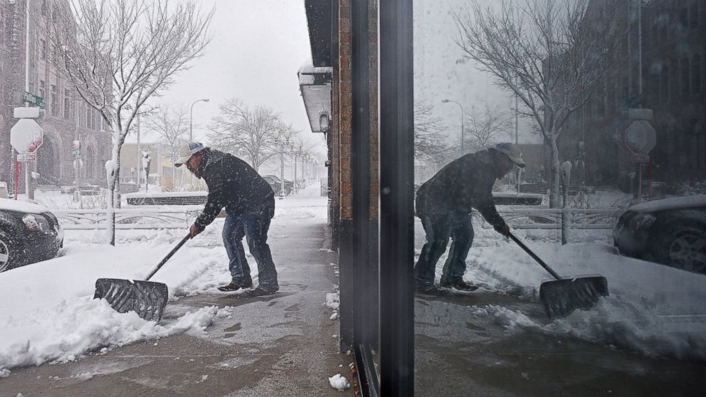 Philip Peter shovels snow in front of the restaurant during a snow storm, Nov. 18, 2016, in Sioux Falls, South Dakota.