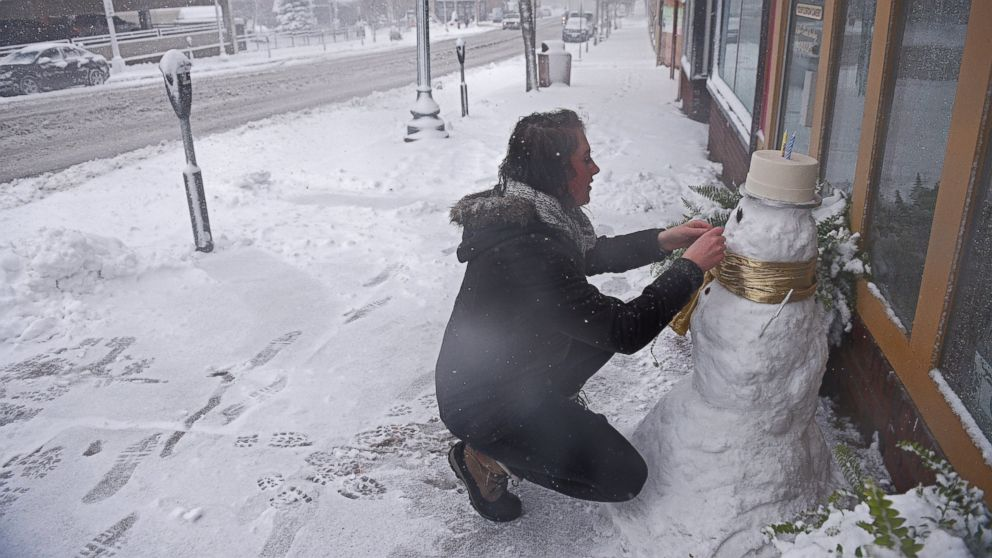 Cassie Maurer, with QT Cakes, puts the finishing touches on a snow man in front of the shop during a snow storm, Nov. 18, 2016, in Sioux Falls, South Dakota.