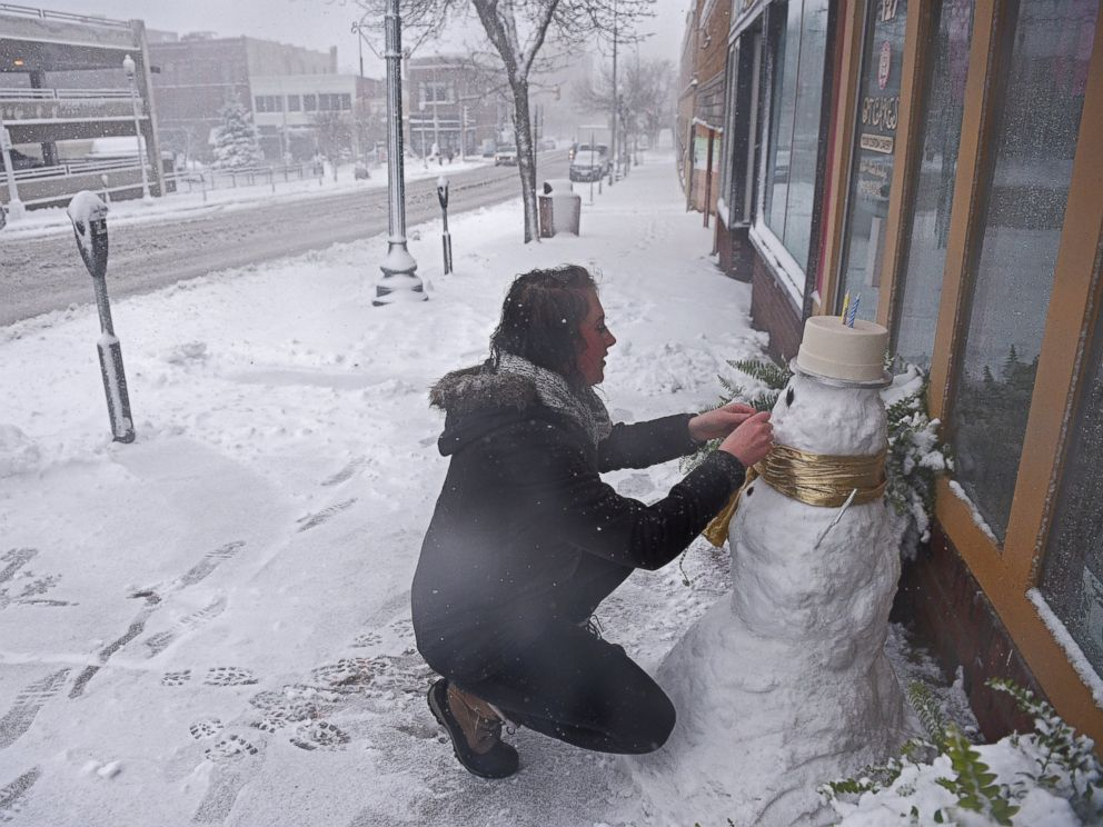 PHOTO: Cassie Maurer, with QT Cakes, puts the finishing touches on a snow man in front of the shop during a snow storm, Nov. 18, 2016, in Sioux Falls, South Dakota.