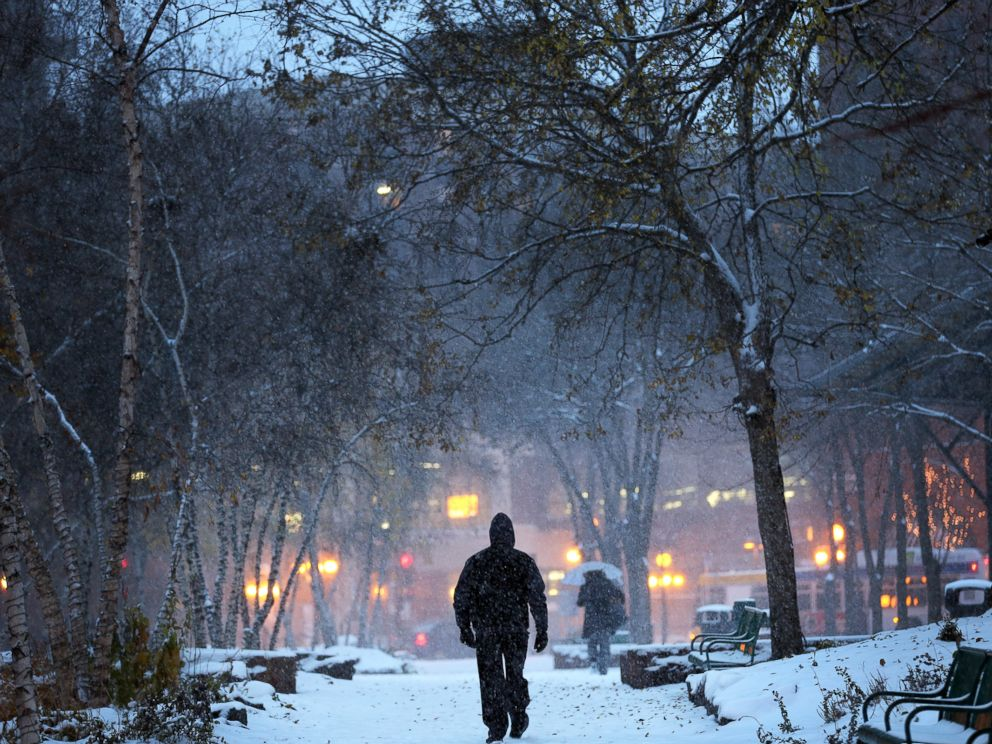 PHOTO: A man walks through Mears Park in downtown St. Paul, Minn., during the first snowstorm of the season, Nov. 10, 2014.