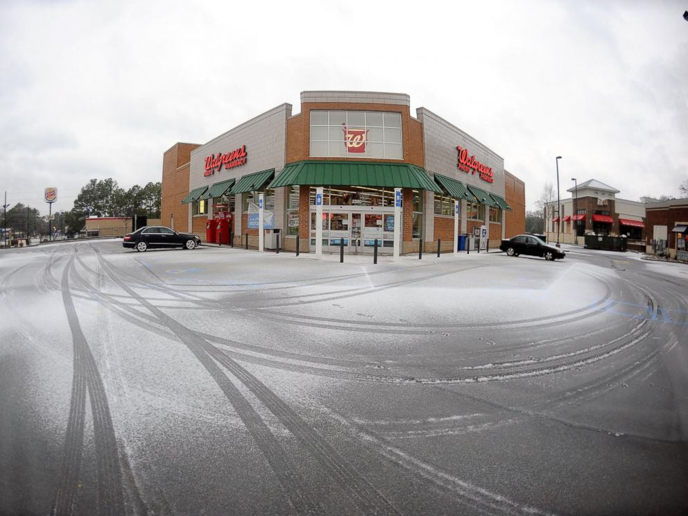 PHOTO: Snow covers the parking area of a a nearly vacant pharmacy, Feb. 12, 2014, in Atlanta.