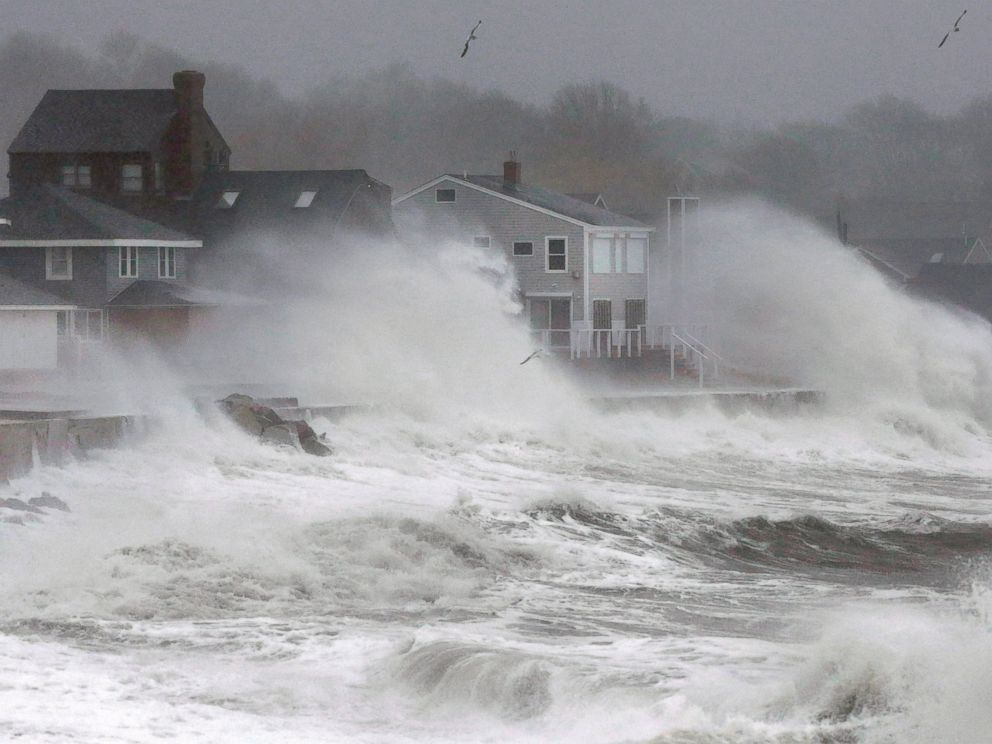 Waves splash against a seawall and onto houses along the Atlantic coast, Tuesday, Dec. 9, 2014, in Scituate, Mass.