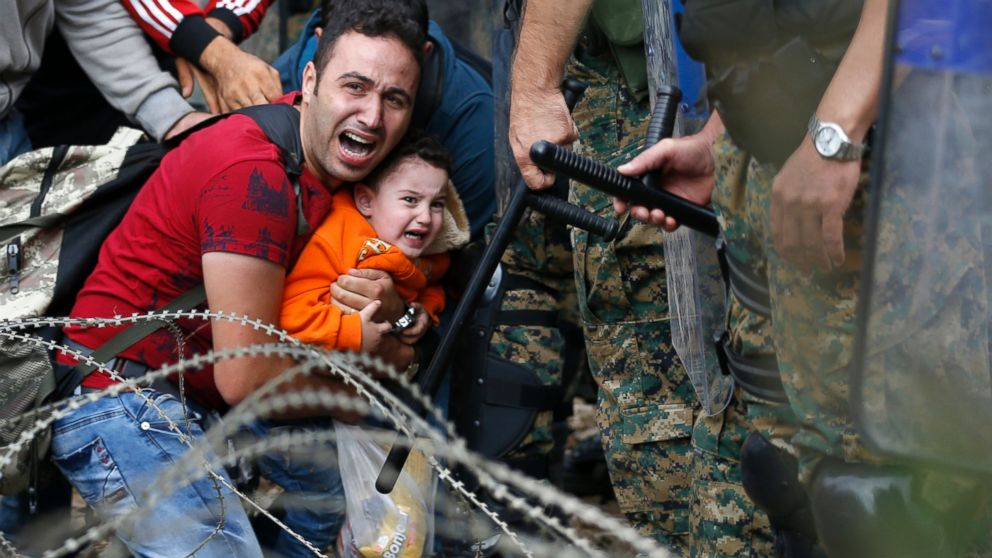 A refugee holding a boy react as they are stuck between Macedonian riot police officers and refugees during a clash near the border train station of Idomeni, northern Greece, Aug. 21, 2015.