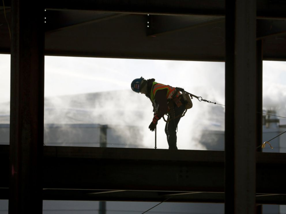 A worker braves cold temperatures while working atop steel beams at the Albany convention center project on Feb. 12, 2016, in Albany, N.Y.