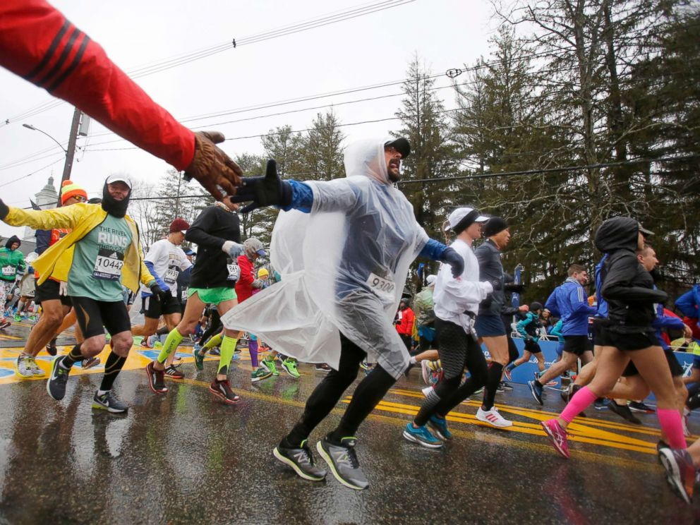 PHOTO: Wearing a plastic poncho, Manuel Gonzalez (9300), from Illinois, reaches out for a high-five just after crossing the starting line during the 122nd running of the Boston Marathon, April 16, 2018.