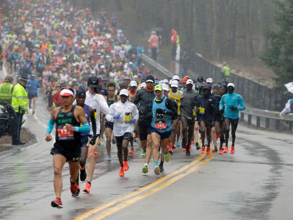 PHOTO: Qixiang Zhou, left, of China, leads a pack of runners during the 122nd Boston Marathon, April 16, 2018, in Boston.