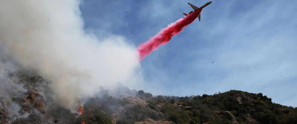 PHOTO: A firefighting aircraft drops the fire retardant Phos-Chek during a wildfire threatening a nearby hillside home in the Pacific Palisades neighborhood on October 21, 2019 in Los Angeles, California. (Photo by Mario Tama/Getty Images)