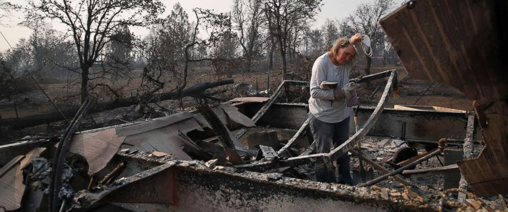 PHOTO: Alyson Kohl wipes her face as she combs through the charred remains of her home burned in the Carr Fire, Saturday, Aug. 11, 2018, in Redding, Calif.