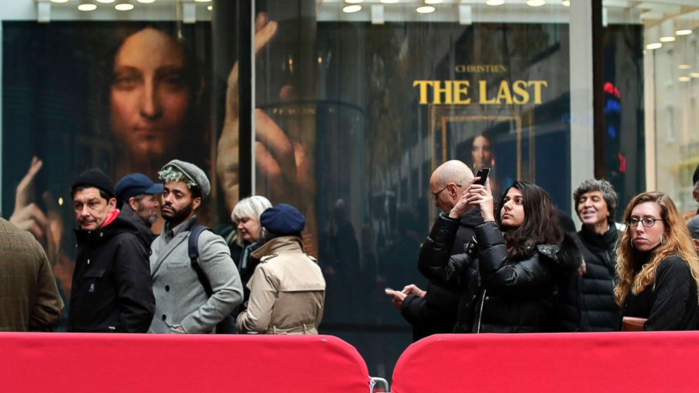 """Visitors wait outside Christie's to view Leonardo da Vinci's """"Salvator Mundi"""", Nov. 14, 2017, in New York. The painting is expected to sell at auction for $100 million on Wednesday."""