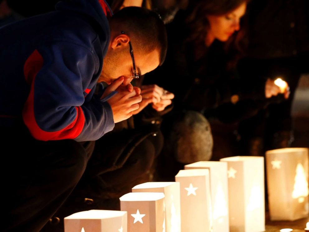 PHOTO: A man reacts placing candles on a makeshift memorial in honor of the victims who died a day earlier when a gunman opened fire in an elementary school, Dec. 15, 2012, in Newtown, Conn.